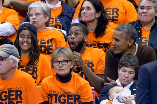 COLLEGE PARK, MD - MARCH 21:  (AFP OUT) U.S. President Barack Obama (R) sits with his nephew Avery Robinson (C) and daughter Malia (L) while attending the Green Bay versus Princeton women's college basketball game in the first round of the NCAA tournament, March 21, 2015 in College Park, Maryland. President Barack Obama's niece Leslie Robinson plays for Princeton.  (Photo by MIchael Reynolds-Pool/Getty Images)