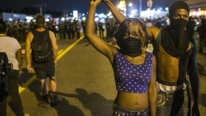 Two anti-police demonstrators walk away from a line of St Louis County police officers during protests in Ferguson, Missouri