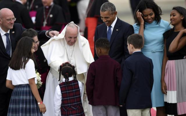 Pope Francis greets children as he is escorted by President Barack Obama after arriving at Andrews Air Force Base in Md., Tuesday, Sept. 22, 2015. The Pope is spending three days in Washington before heading to New York and Philadelphia. This is the Pope's first visit to the United States. First lady Michelle Obama, second from right, and Sasha Obama, right, watch. (AP Photo/Susan Walsh)