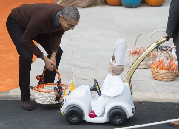 """US President Barack Obama greets a young child dressed as the Pope and riding in a """"Popemobile"""" as he hands out treats to children trick-or-treating for Halloween on the South Lawn of the White House in Washington, DC, October 30, 2015. AFP PHOTO / SAUL LOEB        (Photo credit should read SAUL LOEB/AFP/Getty Images)"""