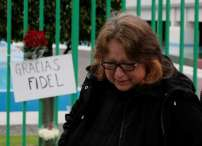 A woman reacts next to a placard and flowers as part a tribute outside the Cuban Embassy in Mexico, following the announcement of the death of Cuban revolutionary leader Fidel Castro, in Mexico City