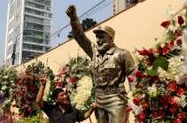 A man poses for a picture next to a statue of Cuban revolutionary leader Fidel Castro with flowers as part of the tribute following the announcement of his death inside the Cuban embassy in Lima