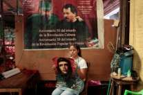 A woman poses for a photograph near a poster of late former Cuban leader Fidel Castro and Nicaragua's President Daniel Ortega in Managua