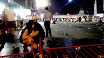 People take cover at the Route 91 Harvest country music festival after a gunman opened fire at a crowd of concertgoers. At least 50 people were killed and hundreds were hurt in the mass shooting