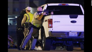 A police officer takes cover behind a truck at the scene of a shooting near the Mandalay Bay resort and casino on the Las Vegas Strip, Sunday, Oct. 1, 2017, in Las Vegas. Multiple victims were being transported to hospitals after a shooting late Sunday at a music festival on the Las Vegas Strip