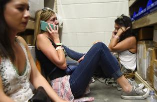 Powers Imagery/Powers Imagery/Invision/AP Women make phone calls while taking shelter inside the Sands Corporation plane hangar after a mass shooting in which dozens were killed at Route 91 Harvest Festival on Sunday, Oct. 1, 2017, in Las Vegas. (Al Powers/Invision/AP)