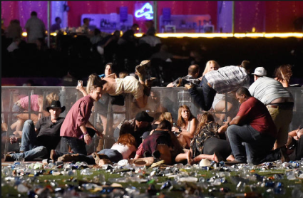 People scramble for shelter at the Route 91 Harvest country music festival after a gunman opened fire on the crowd in Las Vegas. The gunman, identified by police as 64-year-old Stephen Paddock, was found dead in a hotel room at the Mandalay Bay Mandalay Bay Resort and Casino. CREDIT: Getty