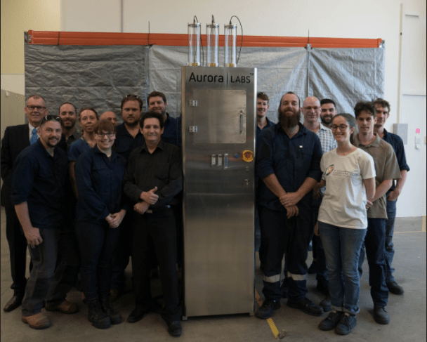 Aurora Labs team with their first printer to ship. Photo via Aurora Labs/Twitter.