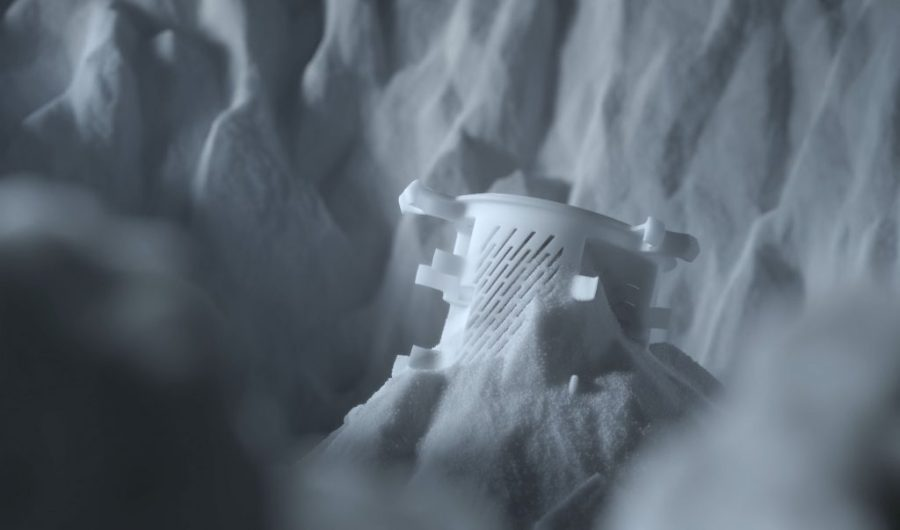 Polymer 3D printed part within the powder bed. Photo via EOS