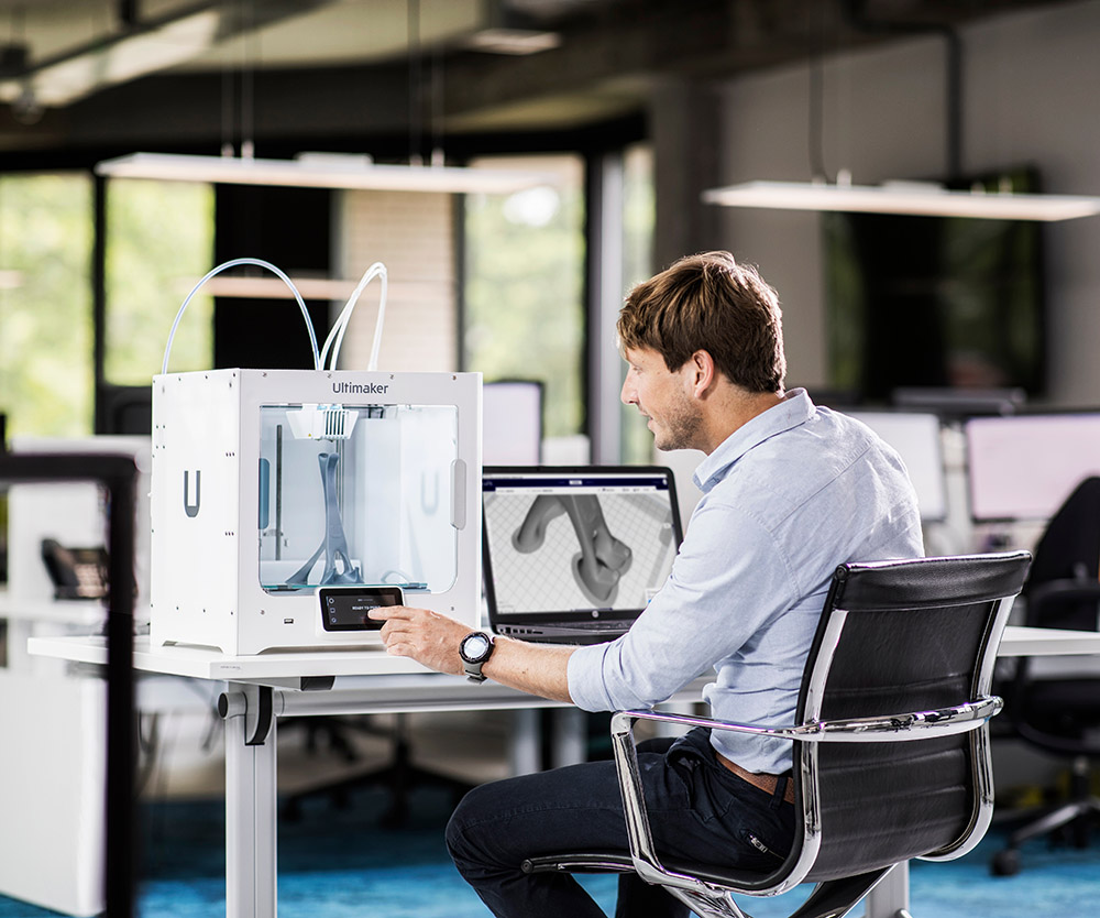 A man sets up a print on his Ultimaker S3 3D printer