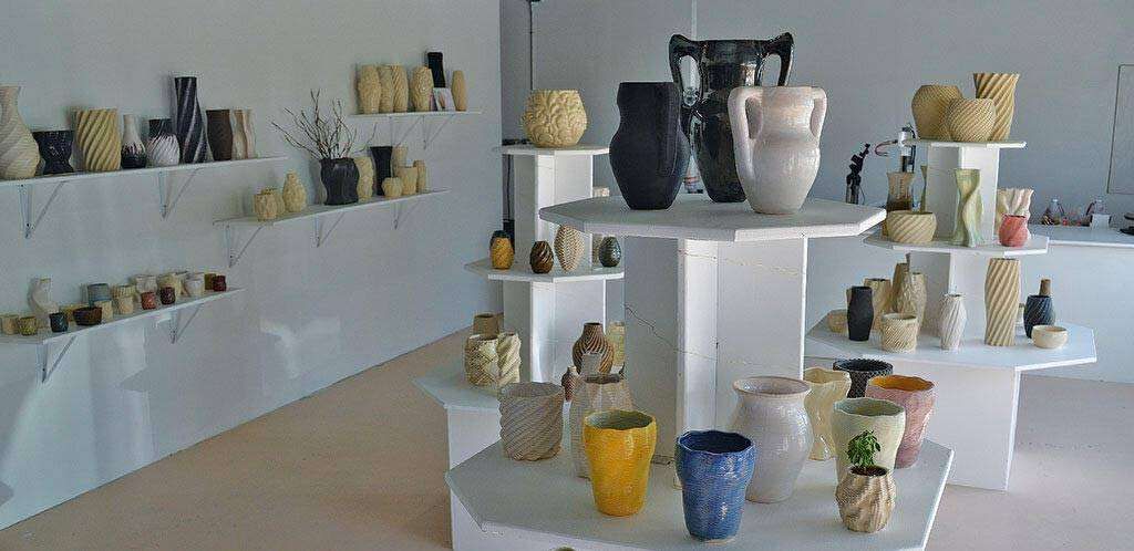 A studio filled with finished 3D printed ceramic pots and vases