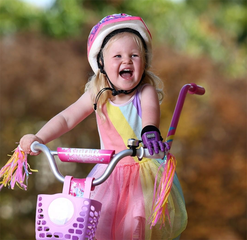 Photo of a young girl riding a bike while using the 3D printed Kinetic hand design