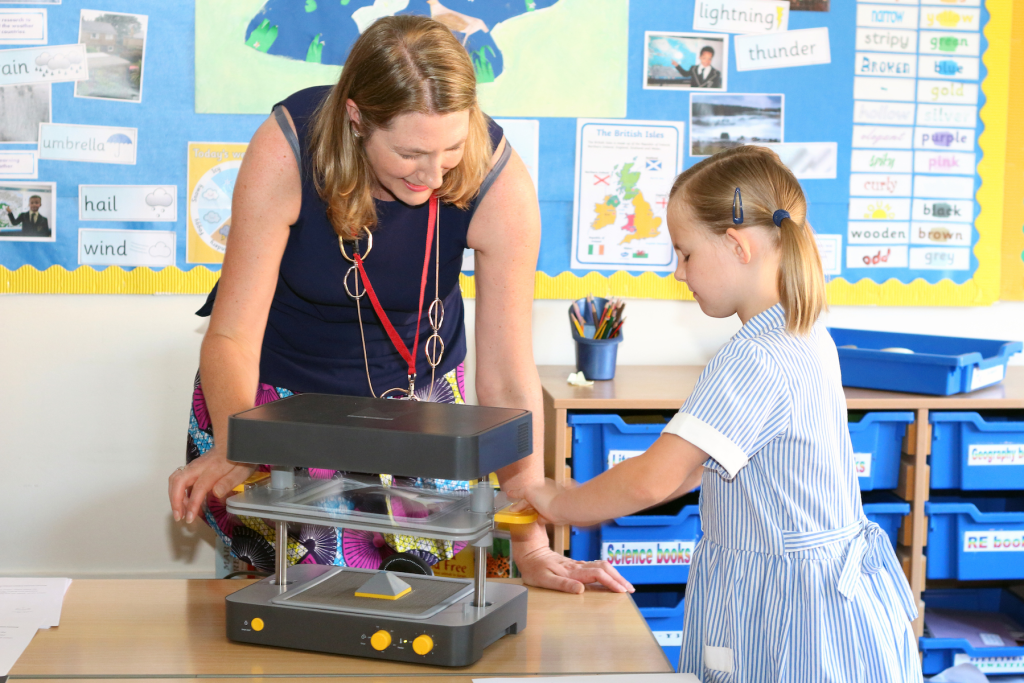 A young girl learning how to use the Mayku FormBox vacuum former at school