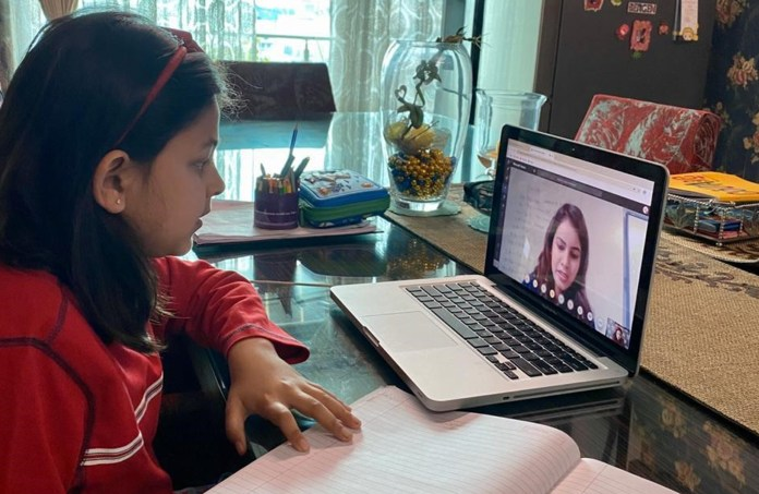 A student interacting with her teacher during online class through Microsoft Teams