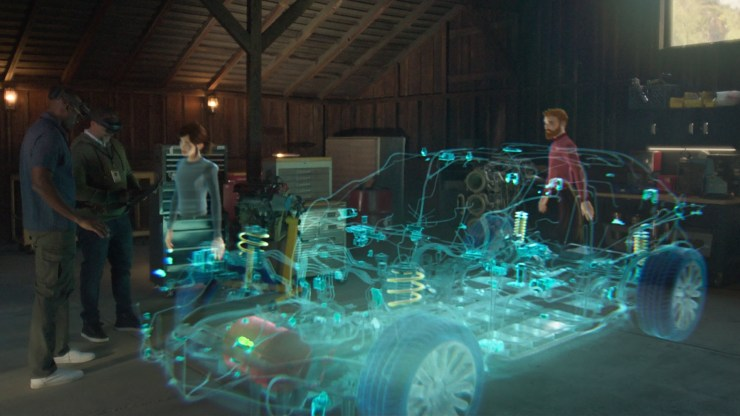 Avatars appear around a three-dimensional hologram of car schematics to illustrate a virtual design review session in mixed reality.