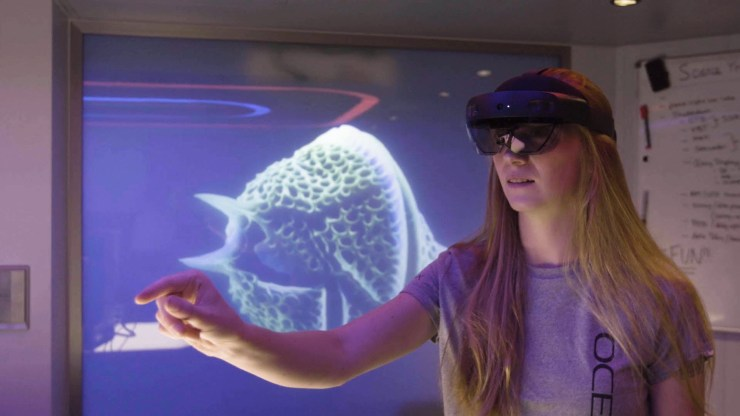 A woman wearing an OceanX shirt and a HoloLens interacts with an unseen hologram with an image of sea life in the background.