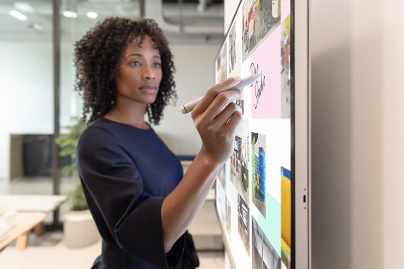 A woman writes on a Surface Hub 2S in an office