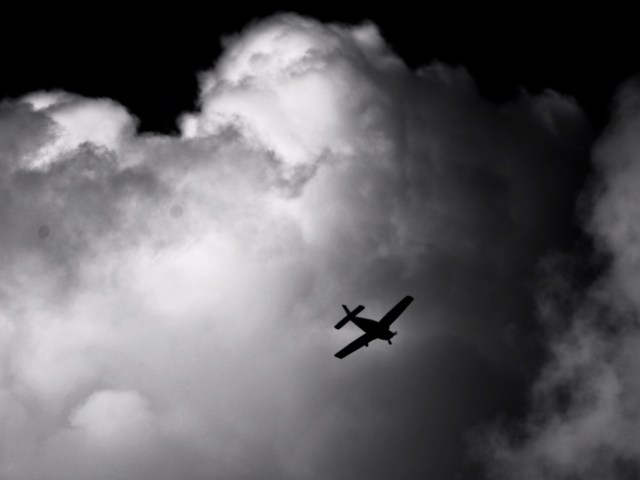 Black and white art print, aircraft flying across cloudy sky