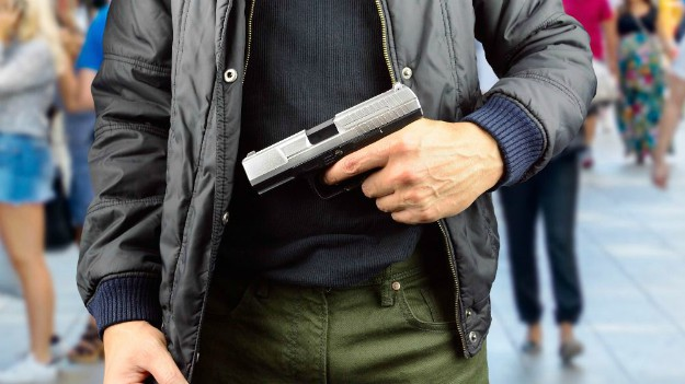 Man holding gun | Global Catastrophes To Prepare For NOW