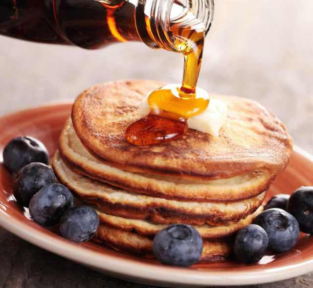 Close-up of pouring maple syrup on stack of pancakes | Survival Food Items That Will Outlast The Apocalypse