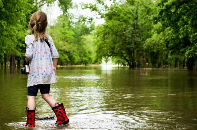 Girl with her camera walking in the flooded road   Flood Survival Tips   How To Survive Before, During, And After A Flood