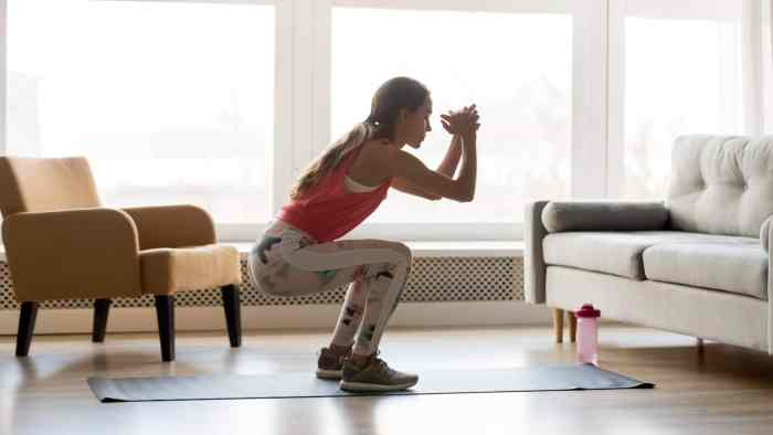 Young woman doing a squat in her living room