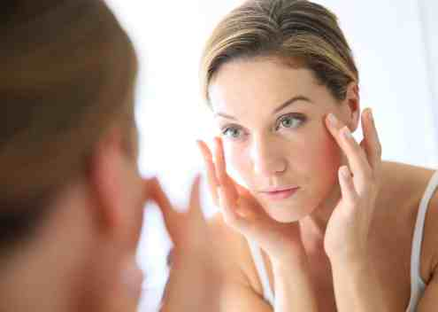 White woman looking in mirror with beautiful healthy skin