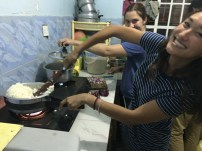 Ariel cooking Ugali, as Sierra cooks some veggies