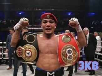 Murodjon Akhmadaliev poses with the IBF and WBA titles.