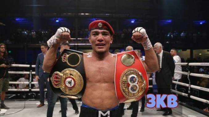 Murodjon Akhmadaliev poses with the IBF and WBA titles.