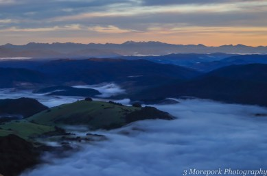 Dawn light on Mt Owen, mist in the valleys, over the Buller River and Lake Rotoiti. (radio mast on Mt. Murchison, left centre) Taken from Mt Robert.