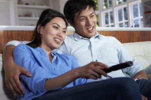 Asian Couple Sitting On Sofa Watching TV Together