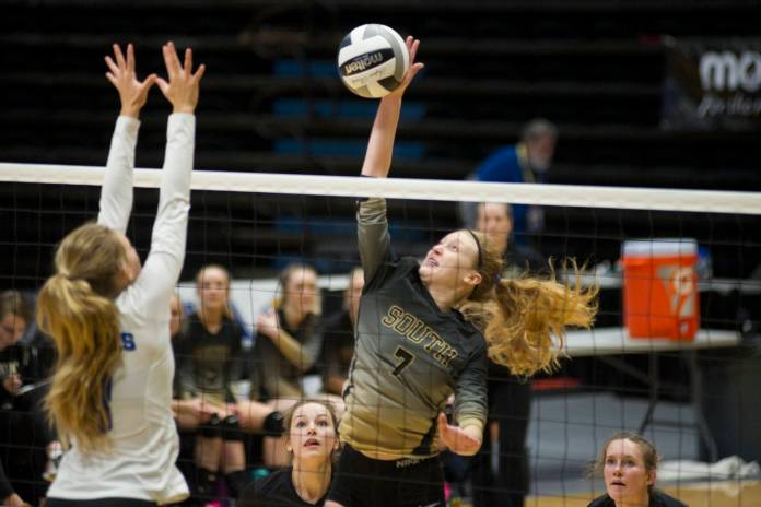 South Anchorage High School-Student Kinsey Schilke trifft den Ball, als Lily Smith von Thunder Mountain bei der ASAA / First National Bank Alaska 3A / 4A-Volleyball-Staatsmeisterschaft am Freitag im Alaska Airlines Center in Anchorage den Block hochfährt. Süd gewann 3: 0 (25-10, 25-21, 25-12). (Nolin Ainsworth | Juneau Empire)