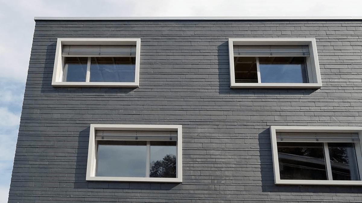 Modernes Haus mit Fensterzargen als Stilelement und grauer Fassade