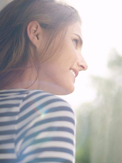 Junge Frau blickt aus Fenster und geniesst die Sonnenstrahlen
