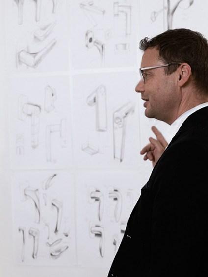 Le responsable de l'innovation, Bodo Gräbner, montre sur un mur des croquis avec de poignées de fenêtres.