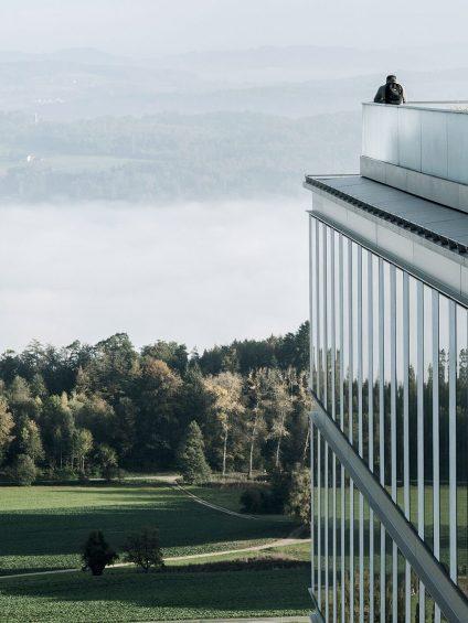 Mann steht auf der Terrasse der Rehaklinik Bellikon und betrachtet die Landschaft