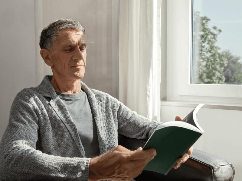 Mann liest entspannt ein Buch vor dem Fenster