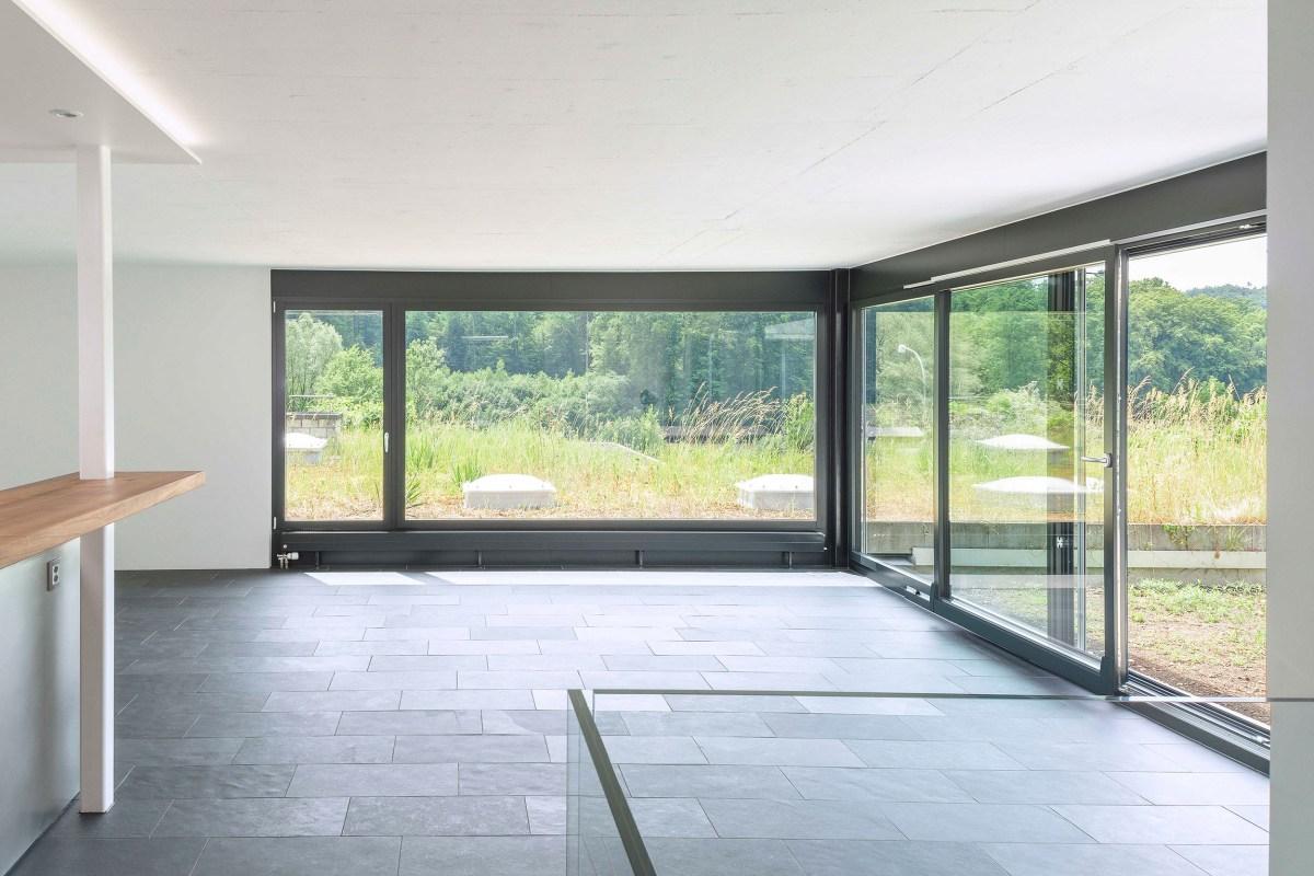 Lichtdurchfluteter Wohnbereich mit grossen Fenstern und Parallelschiebetür.