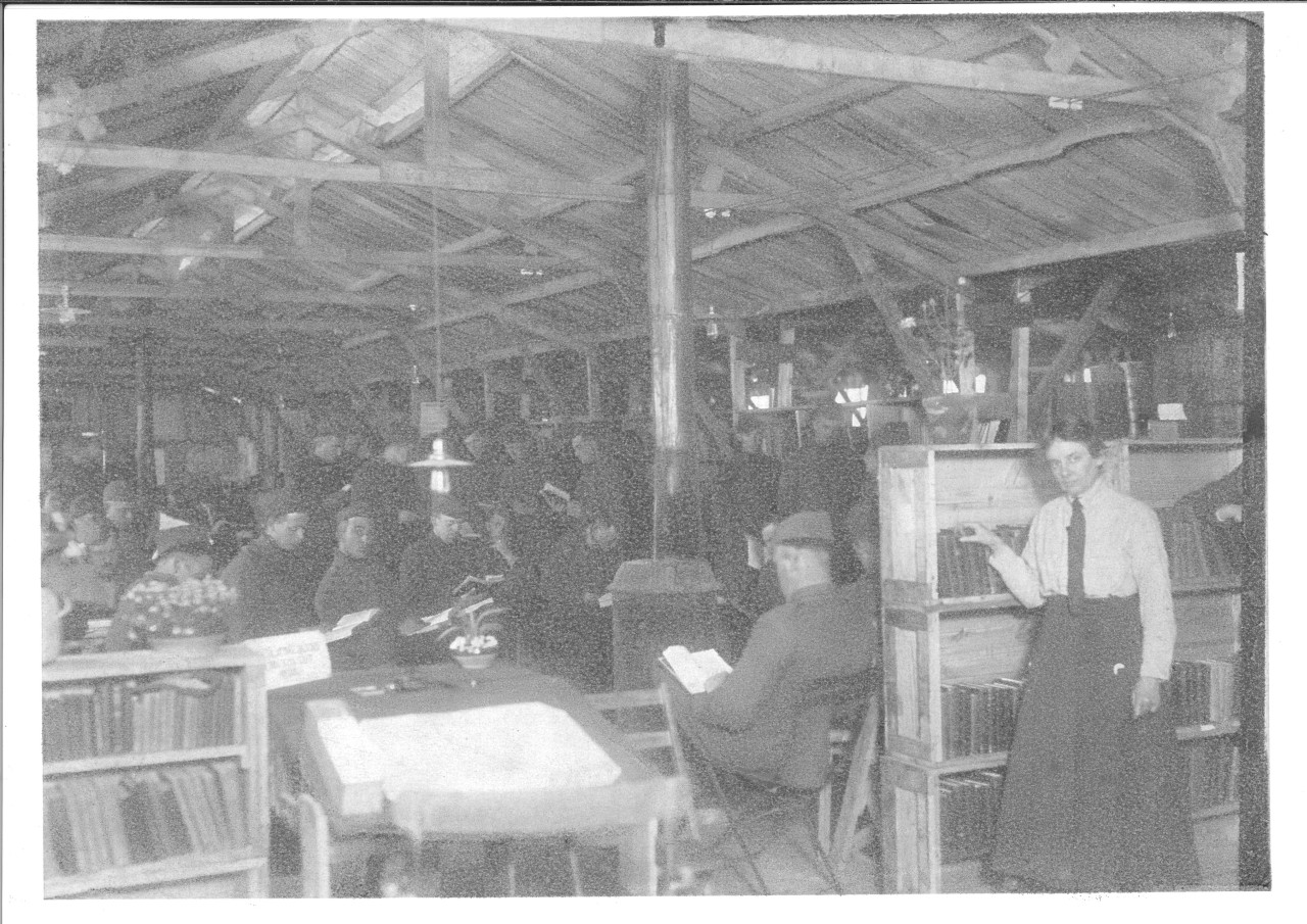 Black and white photograph of military personnel and a librarian in the reading room of the camp library in France.