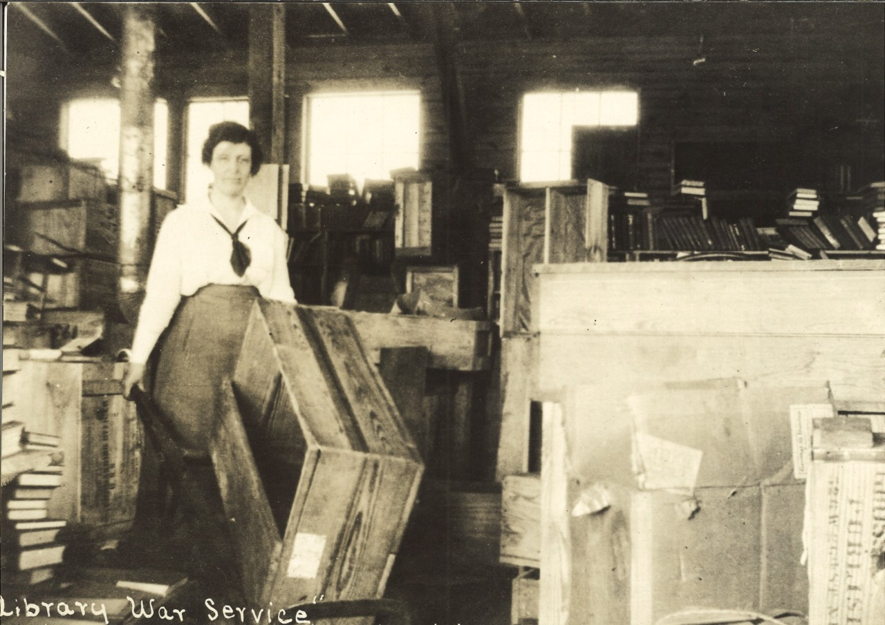 Description: Black and white photograph of a woman carting books at Newport News Dispatch office, VA. Notes on back of photo: Library war service, Newport news dispatch office