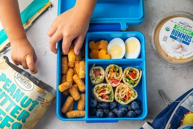Little hands reaching for food in vegetarian bento box