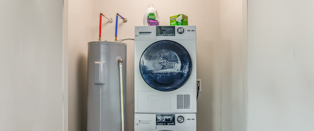 Stacked laundry machine and water heater in a dedicated closet