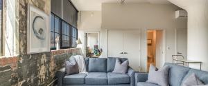 Living room with plus gray couches and an exposed brick wall with large windows