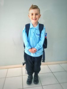 Young boy in his school uniform for the first time in his life.