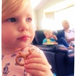 Baby girl eats a pretzel while watching TV