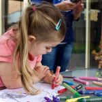 Girl colouring a picture outdoors