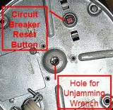View of Bottom of Disposer showing circuit breaker reset button and unjamming wrench hole.