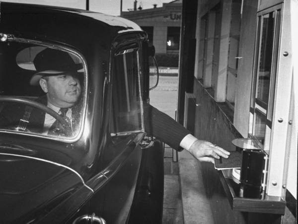 Motorist in his car making a transaction at the drive up window of a bank --ca. 1938.