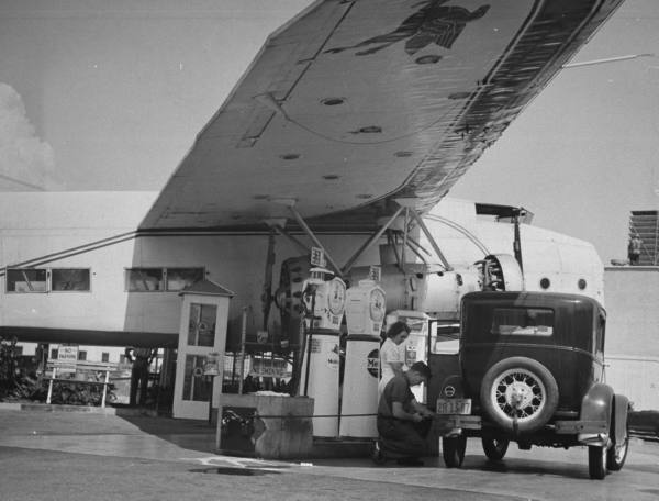 Service attendant pumping gasoline into Ford sedan as woman watches at gas pumps covered by the wing of a large permanently parked airplane, on Wilshire Boulevard --circa 1938.